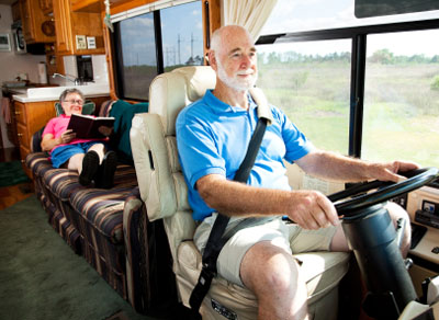 A man drives an RV while his wife sits on a couch behind and reads a book.