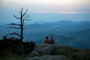 Couple sitting on top of mountain looking over the sunset view