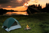 Sunset over a lake with a pitched green tent by a campfire