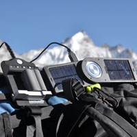 Solar chargers sit atop a backpack with the Himalayas in the background