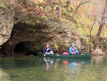 Couple canoeing by water cave on Current River