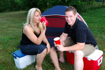 Couple drinking at a campsite sitting on coolers in front of their tent