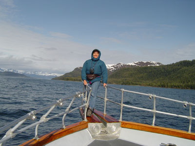 Malia Lane on bow of boat taking cruise on Alaskan glacier