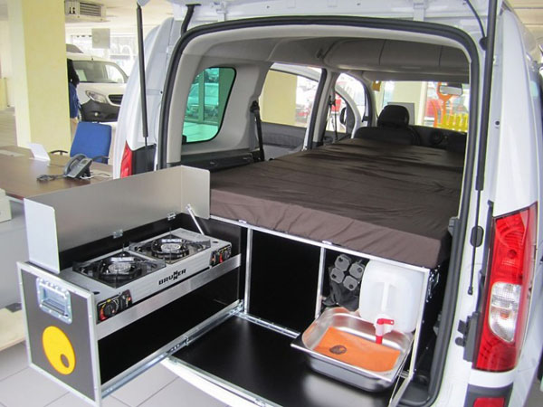QuQuQ with stove, compartments and mattress, in a vehicle