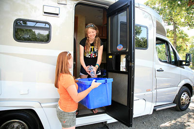 A young girl standing in an RV throws empty water bottles into a blue rectangular recycling basket