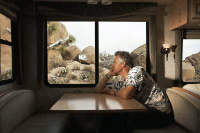 Man sitting at a table in an RV, looking out the window