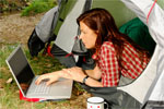 Lady with a laptop lying half out of her tent