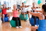 Instructor taking an exercise class at gym using fitness balls
