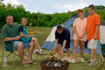 Teenager building a campfire surrounded by his family
