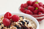 Bowl of oatmeal with raspberries, raisins and almonds