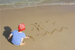 Child drawing sun and surf in sand