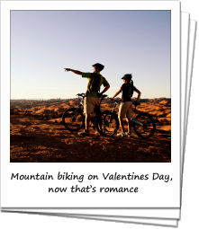 Couple mountain biking on slick rock in Moab, Utah