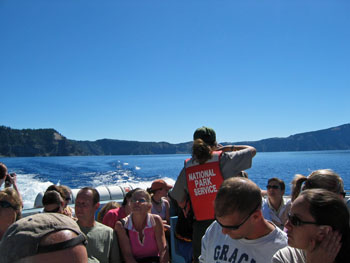 People on moving boat on Crater Lake and lady with red life saving jacket with National Park Service on it