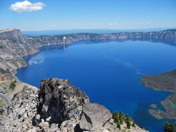 View of deep blue Crater Lake from Watchman Overlook and distant mountains