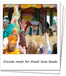 Crowds reach for Mardi Gras Beads from a passing float