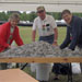 Three older people stand under a tent and over a table filled with soda can tabs