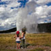 Two young girls watching Old Faithful erupt