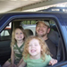 Two girls with father in car