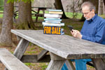Man reading ebook at picnic table with a for sale sign on the pile of books