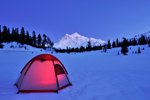 Lit tent perched on snow