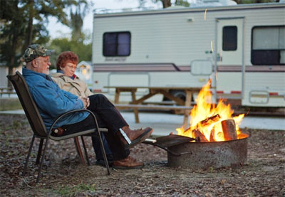 Elderly couple at their campsite enjoying a campfire