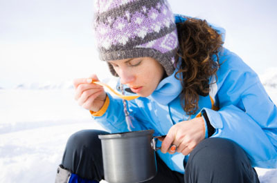 Woman eating soup outdoors in the winter